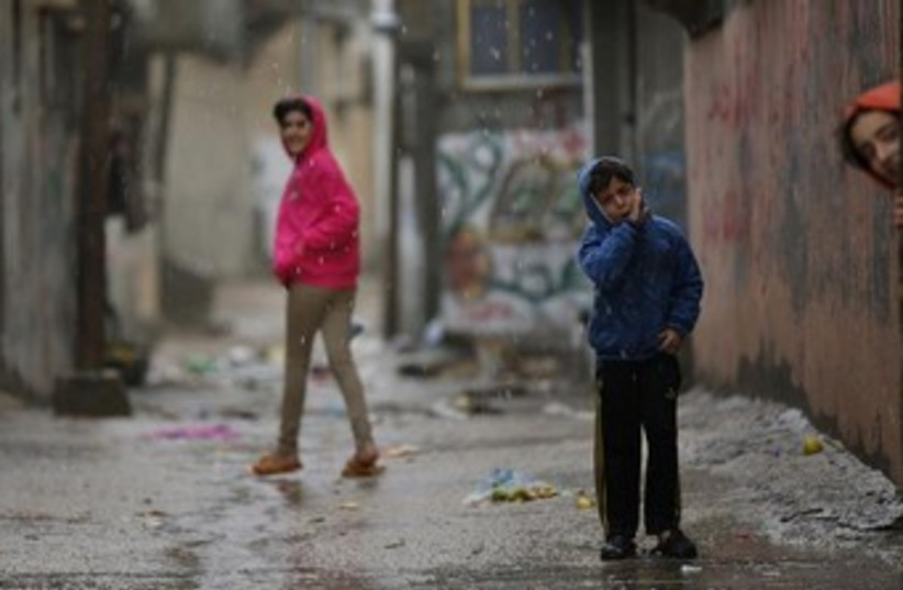 Palestinian children play in rain. [File] (photo credit: Reuters)