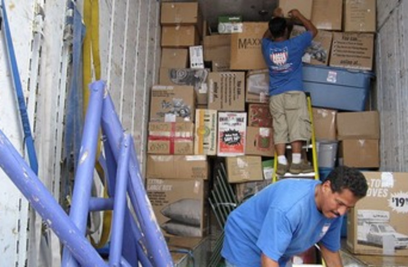 Men load boxes into a moving van. [File] (photo credit: Wikimedia Commons)