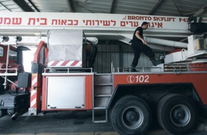 A fireman prepares equipment in Beit Shemesh. (photo credit: Marc Israel Sellem/The Jerusalem Post)