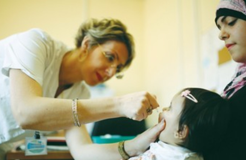 A MEDICAL staffer checks a girl  (photo credit: Marc Israel Sellem/The Jerusalem Post))