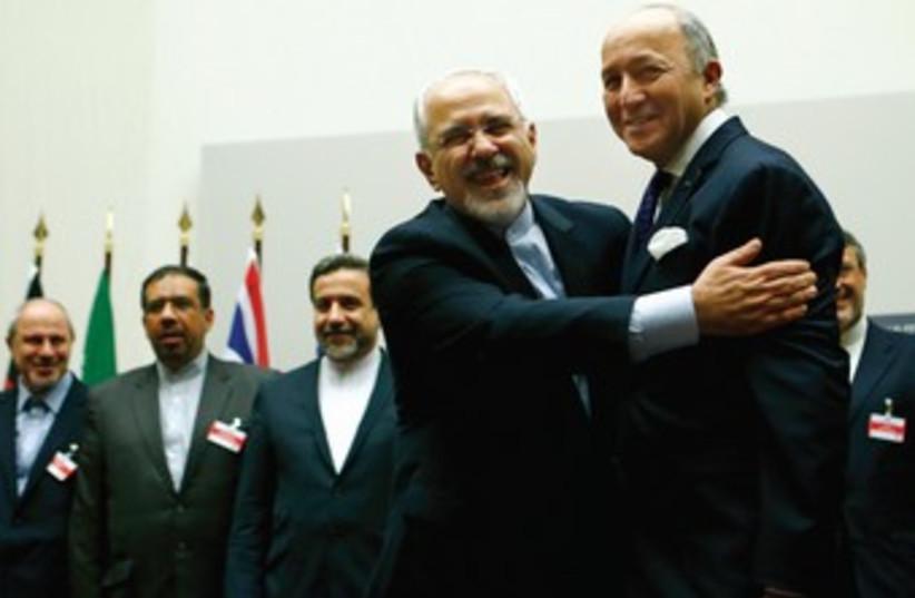 Iranian FM Zarif embraces French FM Laurent (photo credit: REUTERS)