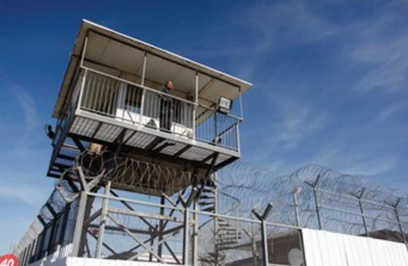 A guard keeps watch from a tower at Ayalon Prison in Ramle. (photo credit: REUTERS)