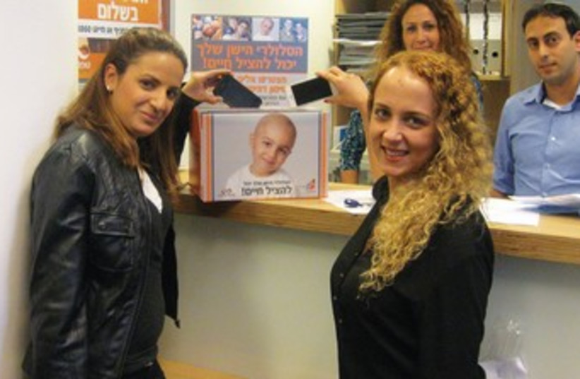Good samaritans drop their old cellphones in a collection box at United Mizrahi Bank. (photo credit: Courtesy)