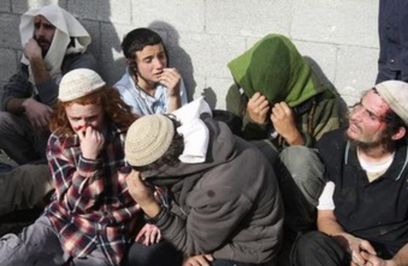 Jewish settlers sit together after being detained by Palestinians, January 7, 2014.  (photo credit: Reuters)