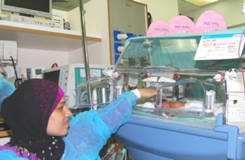 Zinav Alpiomi in hospital with baby.  (photo credit: Courtest Kaplan Medical Center )