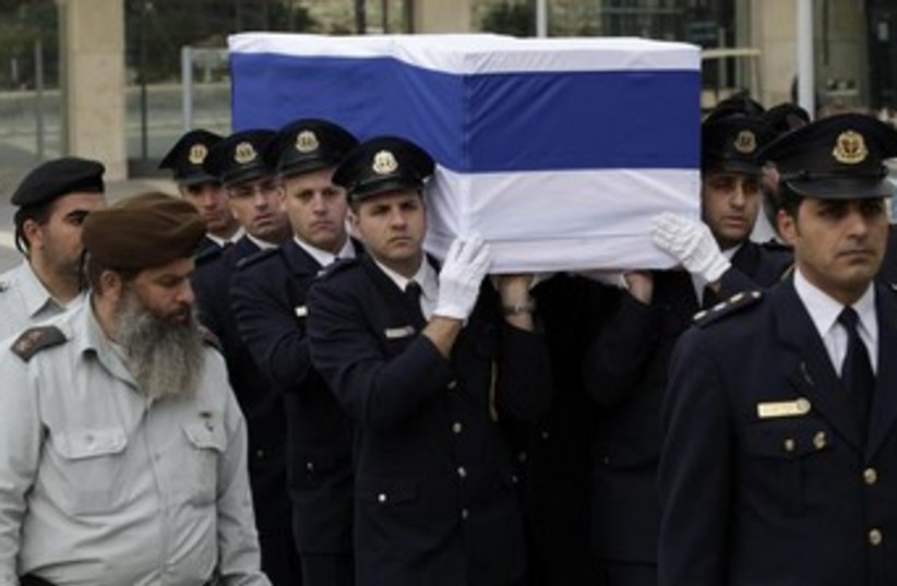 Knesset guard carry former PM Ariel Sharon's coffin, January 12, 2014. (photo credit: REUTERS/Ronen Zvulun)