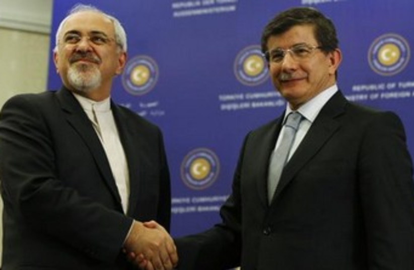 Iranian Foreign Minister Mohammad Javad Zarif shaking hands with Turkish counterpart Ahmet Davutoglu, January 4, 2014. (photo credit: REUTERS/Murad Sezer)