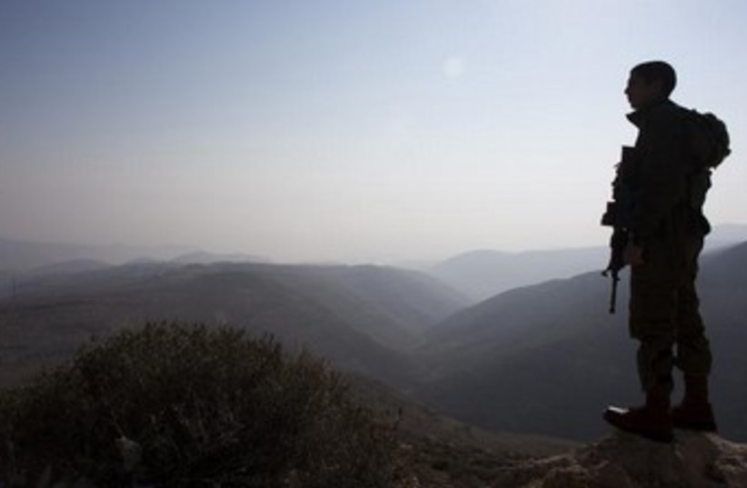 IDF soldier looking over Jordan Valley. (photo credit: REUTERS/Ronen Zvulun)