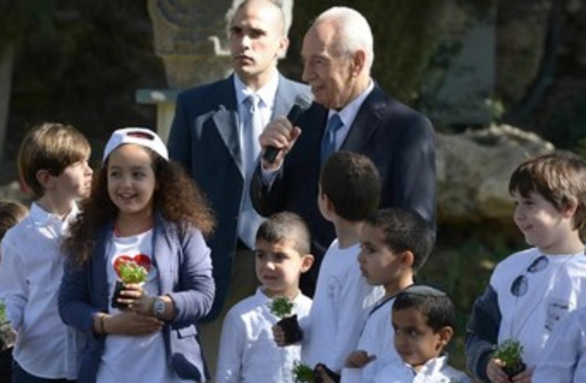 President Shimon Peres planting trees for Tu Bishvat with children at the President's Residence in Jerusalem, January 15, 2014. (photo credit: Mark Neiman/GPO)