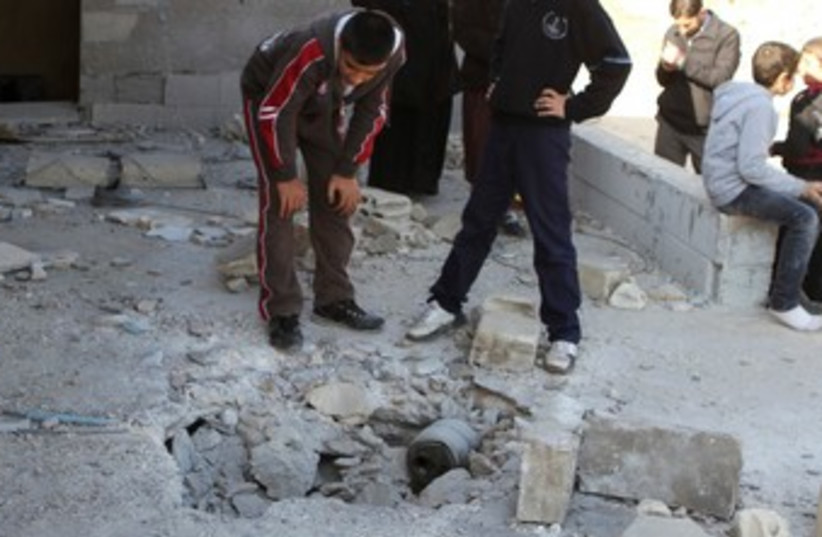 Civilians inspect a site hit by rockets fired from Syria at the Lebanese border town of Arsal January 17, 2014.  (photo credit: REUTERS)