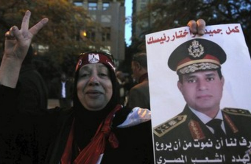 An Egyptian woman holds up a picture of army general Abdel al-Sisi (photo credit: REUTERS)