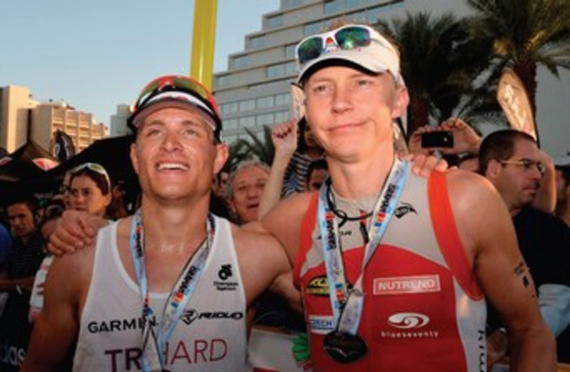 Petr Vabrousek (right) defended his Israman Ironman full distance title in Eilat on Friday, with Israel's Tom Mamarelli (left) finishing in second place overall. (photo credit: AMIT SHISEL)