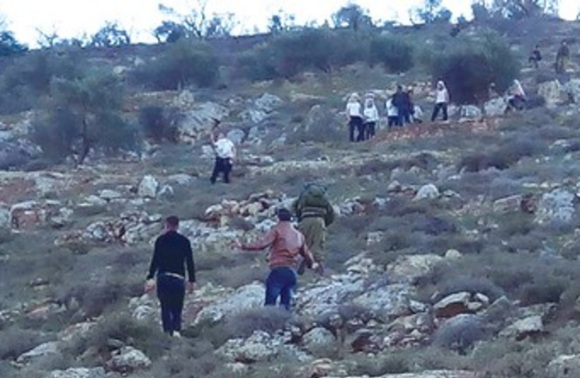 Settlers on a hilltop during clashes with Palestinians Jan 20 2014 (photo credit: ZAKARIYA SADDEH/RABBIS FOR HUMAN RIGHTS)