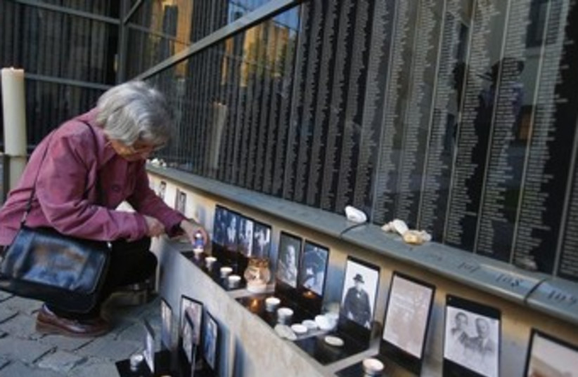 A woman lights a candle at Budapest's Holocaust Memorial Center. (photo credit: REUTERS)