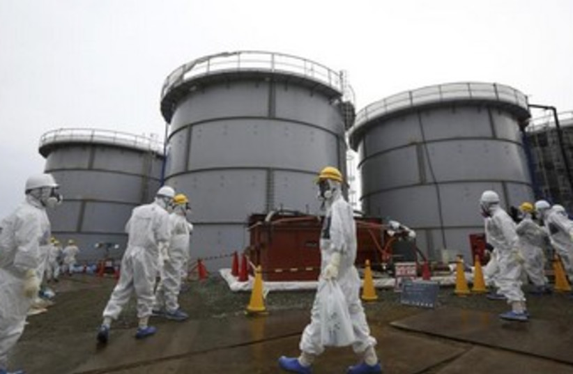 Employees wearing protective suits and masks walk past storage tanks for radioactive water  (photo credit: REUTERS)