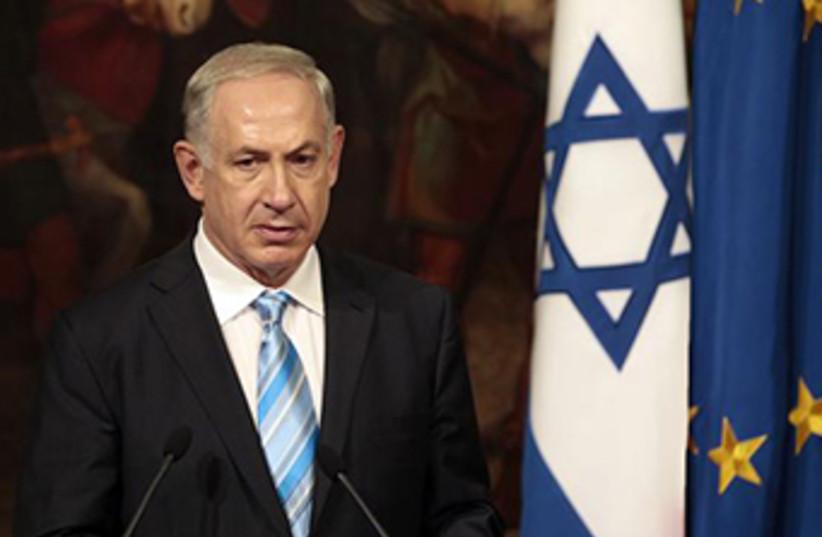 Prime Minister Binyamin Netanyahu backed by Israeli and EU flags (photo credit: REUTERS)