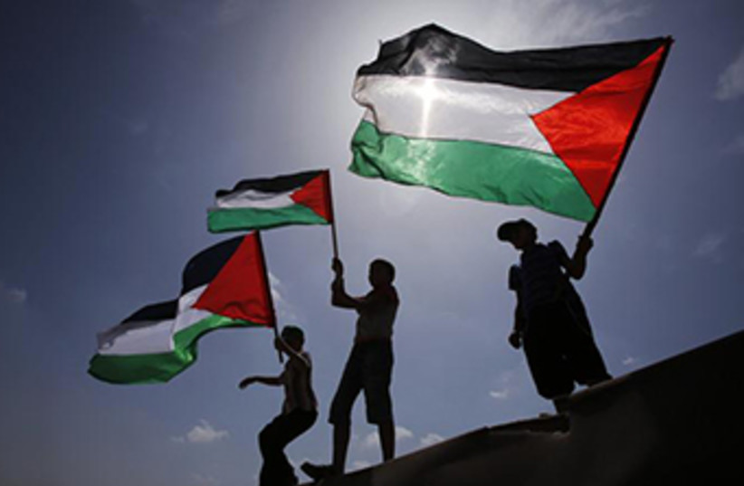 Palestinians wave PLO flags (photo credit: REUTERS)
