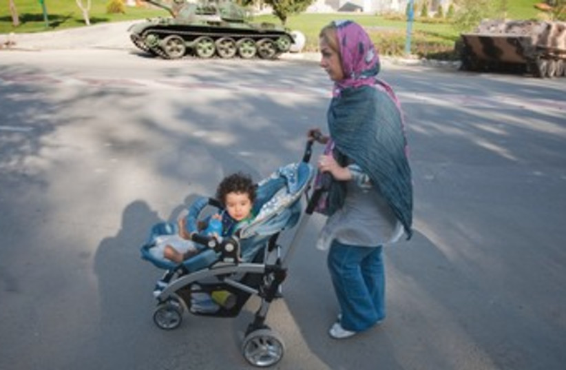 An Iranian woman strolls with her daughter in Tehran. (photo credit: REUTERS)