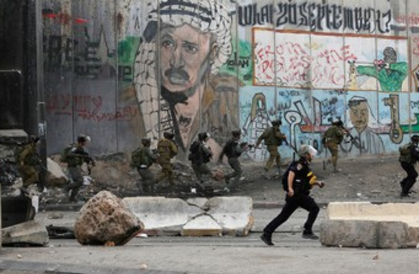 Soldiers and border policemen run past a section of the West Bank security barrier. (photo credit: REUTERS)