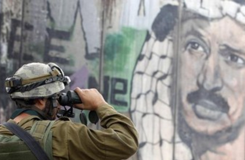 An IDF soldier at  the West Bank security barrier. (photo credit: REUTERS)
