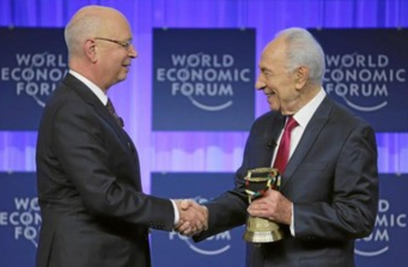 President Shimon Peres receives his award from the World Economic Forum (WEF) honoring him for his long-standing commitment to its mission and his contributions to the annual meeting program for more than two decades, during the WEF in Davos January 24, 2014.  (photo credit: COURTESY OF WORLD ECONOMIC FORUM)