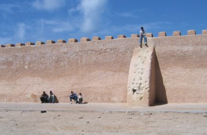 A YOUTH sits on the walls of Essaouira. (photo credit: BEN G. FRANK)