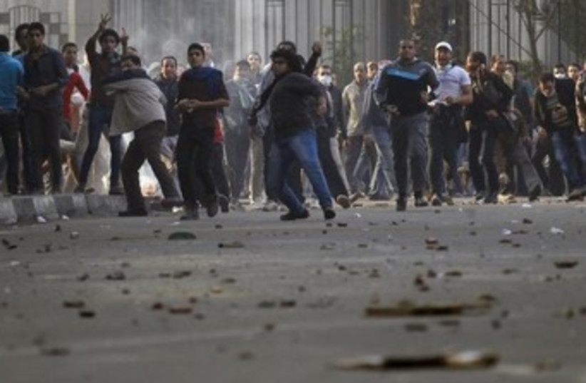 Muslim Brotherhood protesters throw stones and glasses during clashes with supporters of Egypt's army and police in Cairo, January 25, 2014. (photo credit: REUTERS)