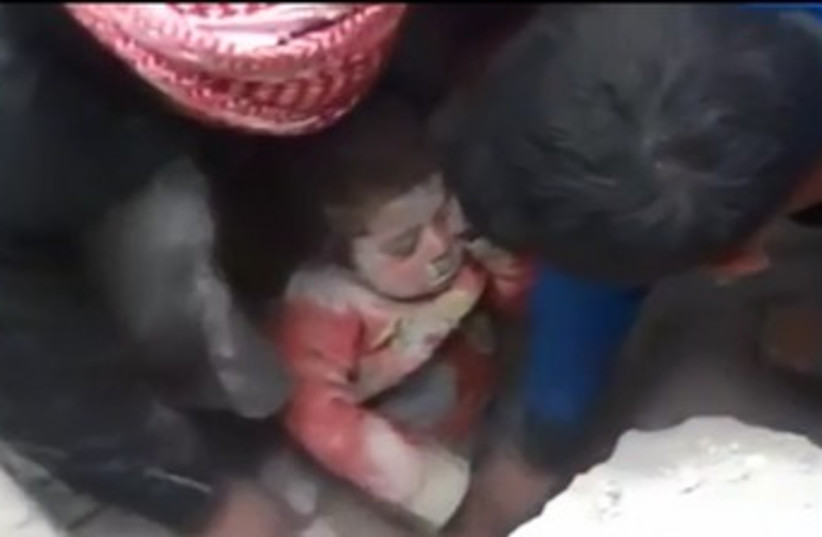 Toddler rescued from rubble in Aleppo, Syria (photo credit: REUTERS)