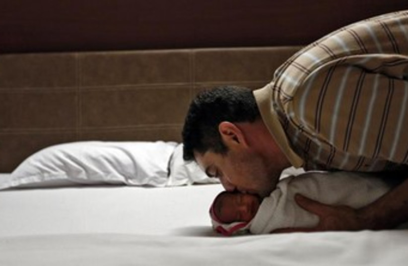 Man with baby born to surrogate mother. (photo credit: REUTERS)