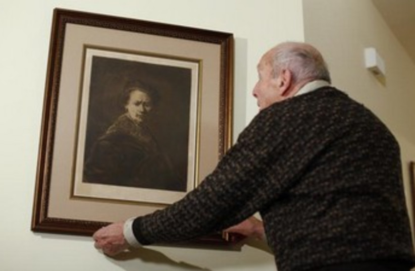"""Harry Ettlinger a former member to the """"Monuments Men"""" with a print of a Rembrandt self-portrait. (photo credit: REUTERS)"""