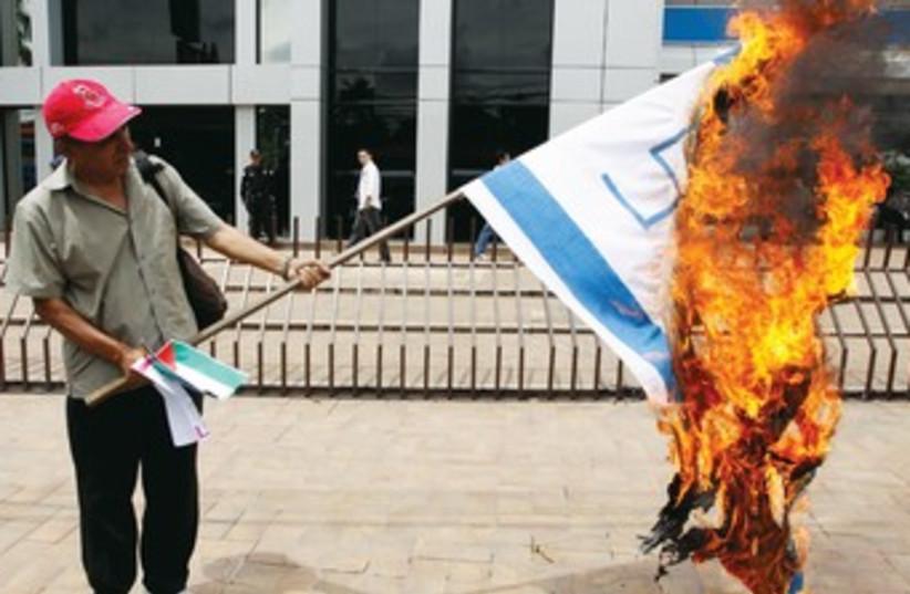 A European burns an Israeli flag. (photo credit: REUTERS)