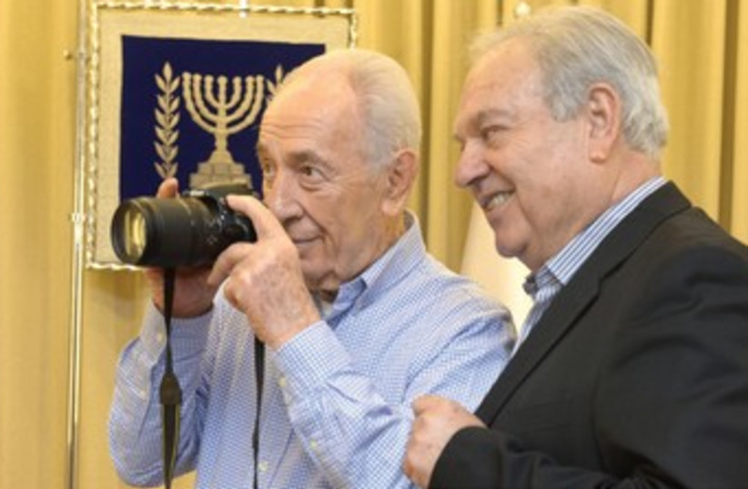 Moshe Milner shows President Shimon Peres how to use his camera. (photo credit: AMOS BEN GERSHOM, GPO)