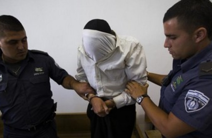 escorted by Israeli prison guards in the Jerusalem District Court (photo credit: REUTERS)
