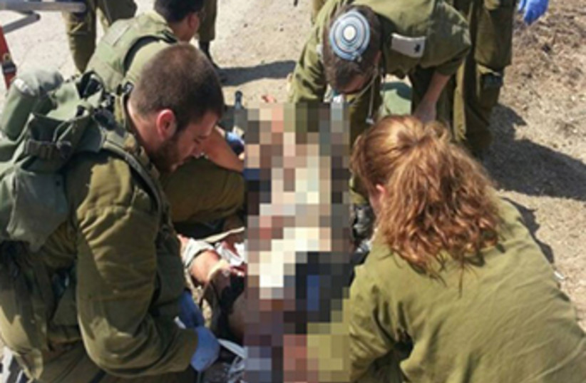 Soldiers in the IDF Medical Corps treat Syrian victims. (photo credit: COURTESY IDF SPOKESMAN'S OFFICE)
