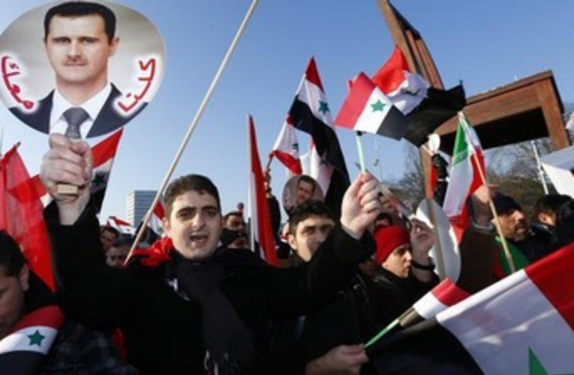 Assad supporters carry Syrian flags and portraits in front of the United Nations European headquarters in Geneva January 31, 2014. (photo credit: REUTERS)