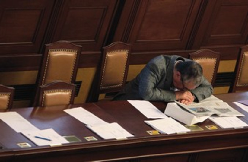 A man places his head on his desk in a fit of exhaustion. (photo credit: REUTERS)
