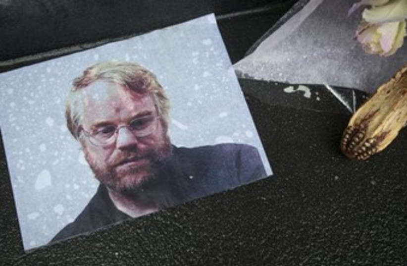 A photo of actor Philip Seymour Hoffman is pictured as part of a makeshift memorial in front of his apartment building in New York February 3, 2014.  (photo credit: REUTERS)