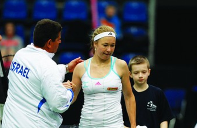 Israel Fed Cup captain Amos Mansdorf (left) consoles Julia Glushko after her defeat to Nadiya Kichenok during the team's 3-0 loss to Ukraine yesterday in Europe/Africa Zone Group I action from Budapest, Hungary. (photo credit: NIR KEIDAR/ISRAEL TENNIS ASSOCIATION)