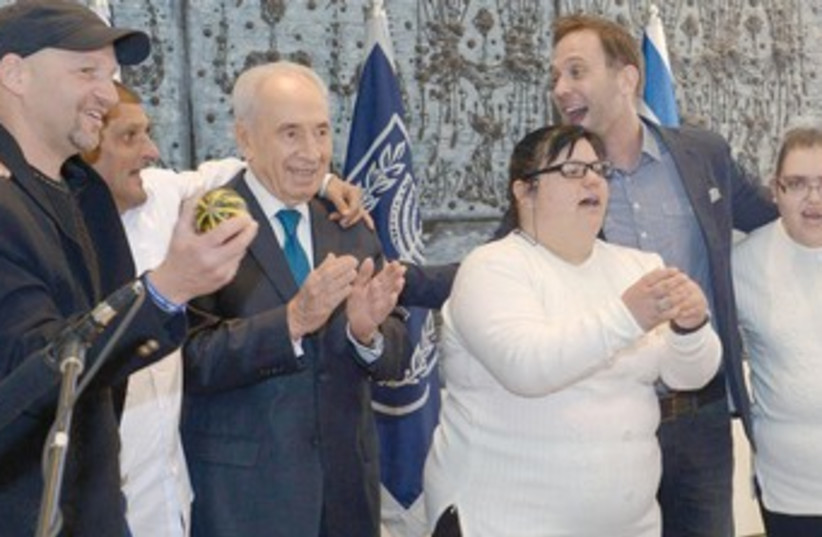 PRESIDENT SHIMON PERES poses with individuals with intellectual disabilities at his residence in the capital yesterday. (photo credit: COURTESY OF THE PRESIDENT'S RESIDENCE)