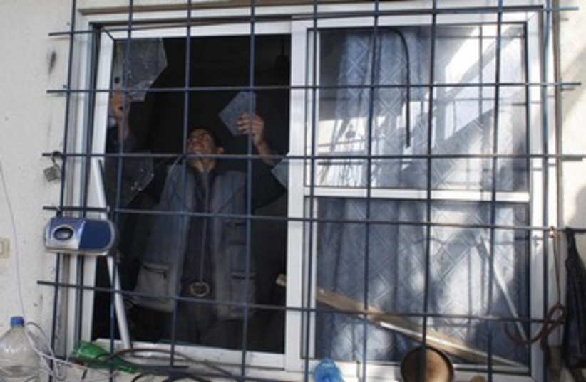 A Palestinian man removes shattered glass from a window of a building after witnesses said it was hit in an Israeli air strike at Nusseirat in the centre of the Gaza Strip (photo credit: REUTERS)