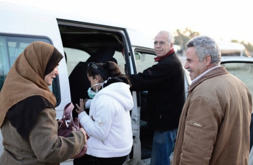 Yuval Roth (second on right) with Mohammed Darajmeh and his daughter Amani at the Eyal checkpoint getting into Roth's van (photo credit: TOMER NEUBERG/FLASH 90)