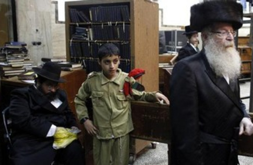 Haredi child dressed in IDF costume for Purim. (photo credit: REUTERS)