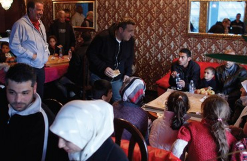 Yank Barry (left standing) with Syrian refugees in Bulgaria. (photo credit: REUTERS)