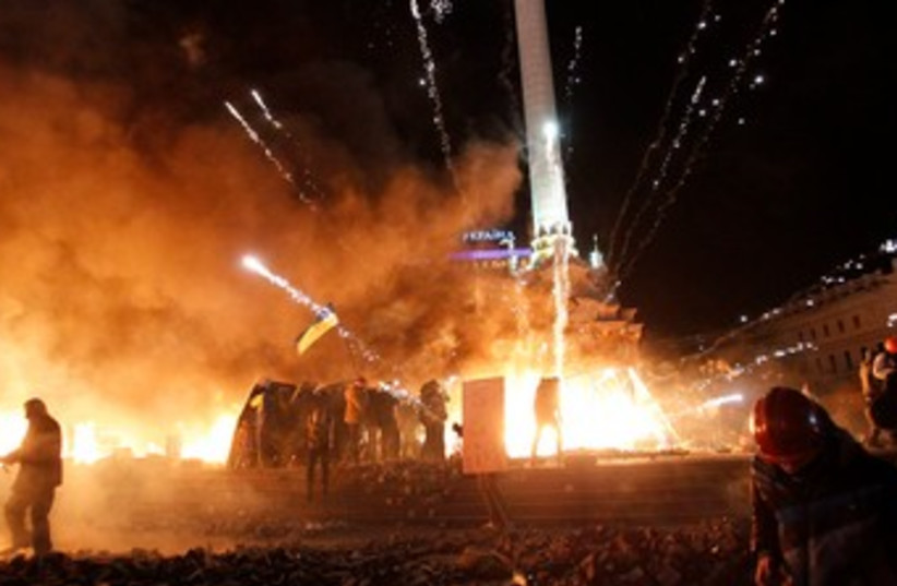 A firework explodes amid flames during clashes between anti-government protesters and riot police at Kiev's Independence Square January 18, 2014. (photo credit: REUTERS)