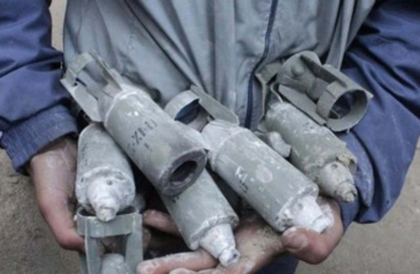 A Syrian boy holds unexploded cluster bombs in Aleppo. (photo credit: REUTERS)
