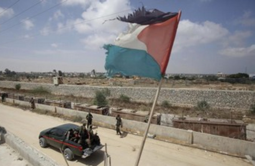 A Palestinian flag flutters above members of the Hamas security forces. (photo credit: REUTERS)