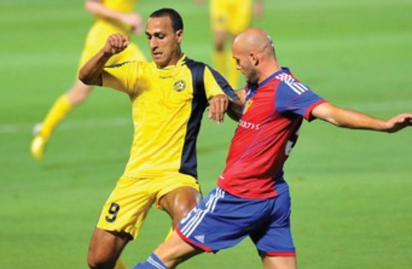 Maccabi Tel Aviv's Maharan Radi (left) and FC Basel's Arlind Ajeti (right) are set to resume battle when their teams meet in the Europa League roundof- 32 first leg at Bloomfield Stadium. Basel knocked out Maccabi in the third qualifying round of the Champions League earlier this season.  (photo credit: ASAF KLIGER)