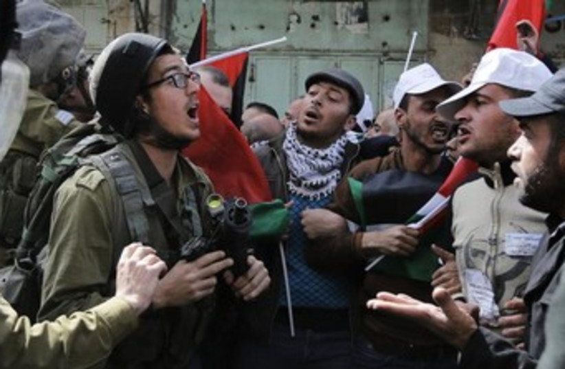Palestinian protesters confront an Israeli soldier during clashes in Hebron, February 21, 2014.   (photo credit: REUTERS)
