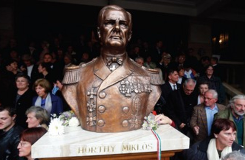 RIGHT-WING DEMONSTRATORS march past a bust of the late Hungarian fascist leader Miklos Horthy. (photo credit: REUTERS)