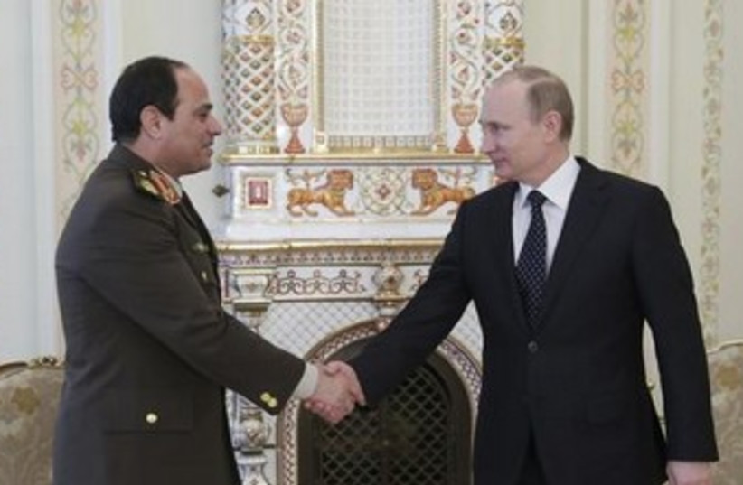 Russian President Vladimir Putin (R) shakes hands with Egypt's Army chief Field Marshal Abdel Fattah al-Sisi. (photo credit: REUTERS)